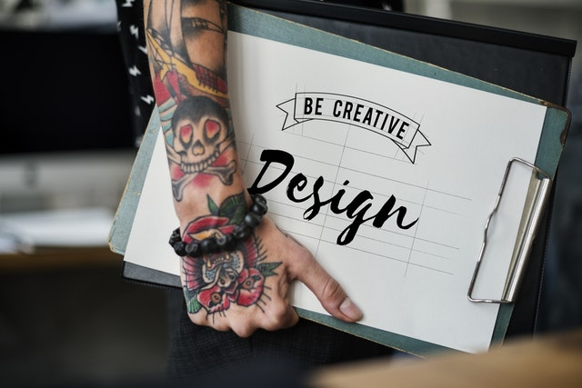 image of a person's arm carrying a notepad with the word design showing prominently