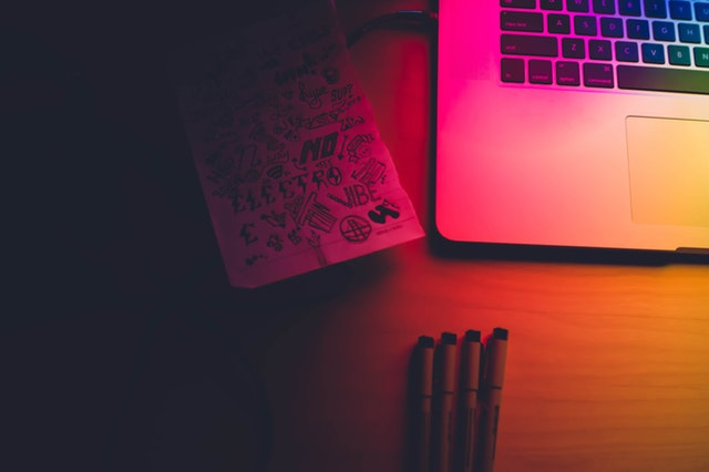 image reinforces website design principle of consistency - image of pencils, the corner of a laptop with a pink glow lighting effect on the overall image